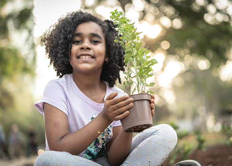 tree planting - girl with potted tree